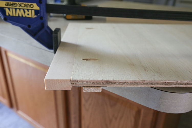 A clamp used to attach 1x2 board to plywood board with pocket holes