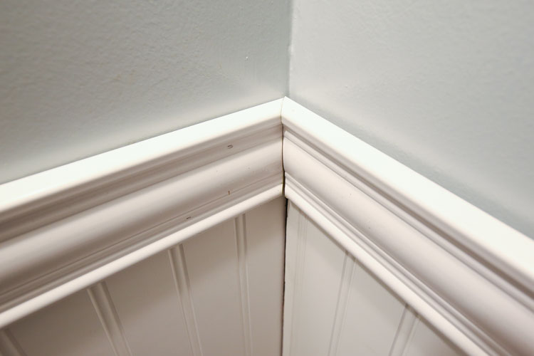 bathroom wall corner with two moulding pieces connecting at a 45 degree angle
