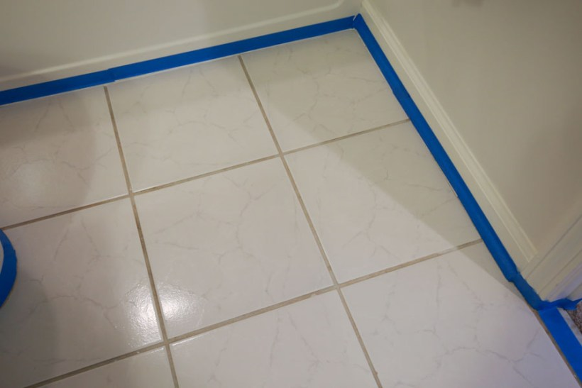 Painters tape being used to tape off the floor trim and bathtub