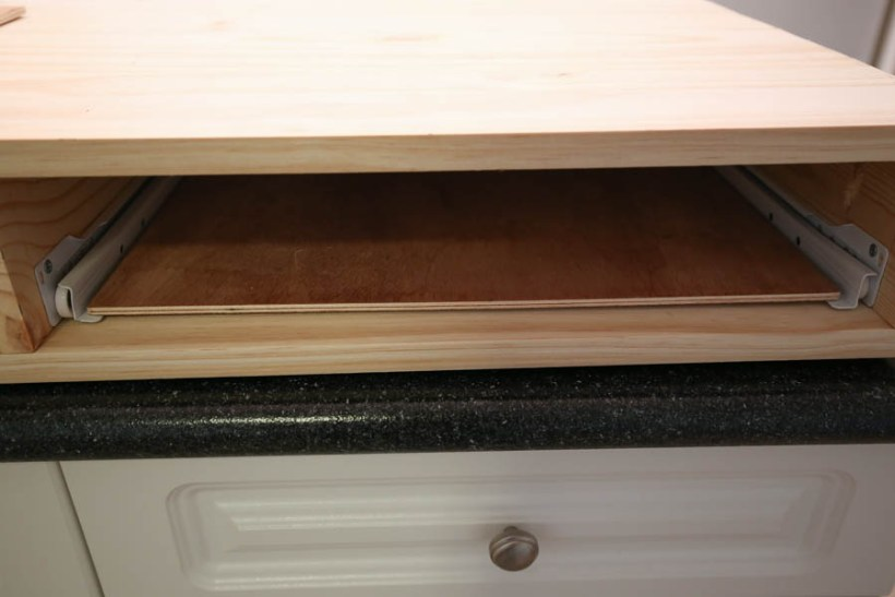 place plywood board between drawer slides to ensure a good fit