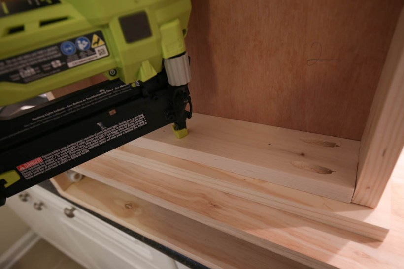 Attaching the drawer faces to the makeup vanity with a brad nailer from the inside of the drawer