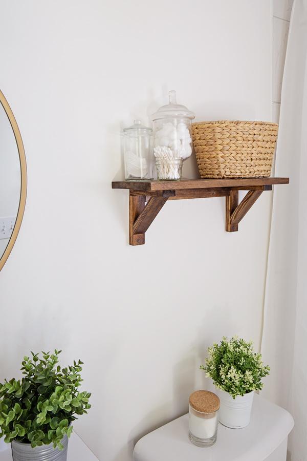 Wood floating shelf over toilet for extra bathroom storage