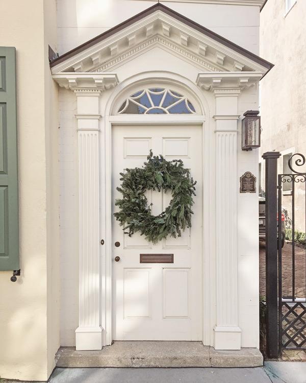 bushy green Christmas wreath on white front door in Charleston