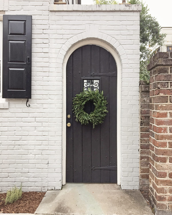 Simple boxwood wreath on black door in Charleston for Christmas decor