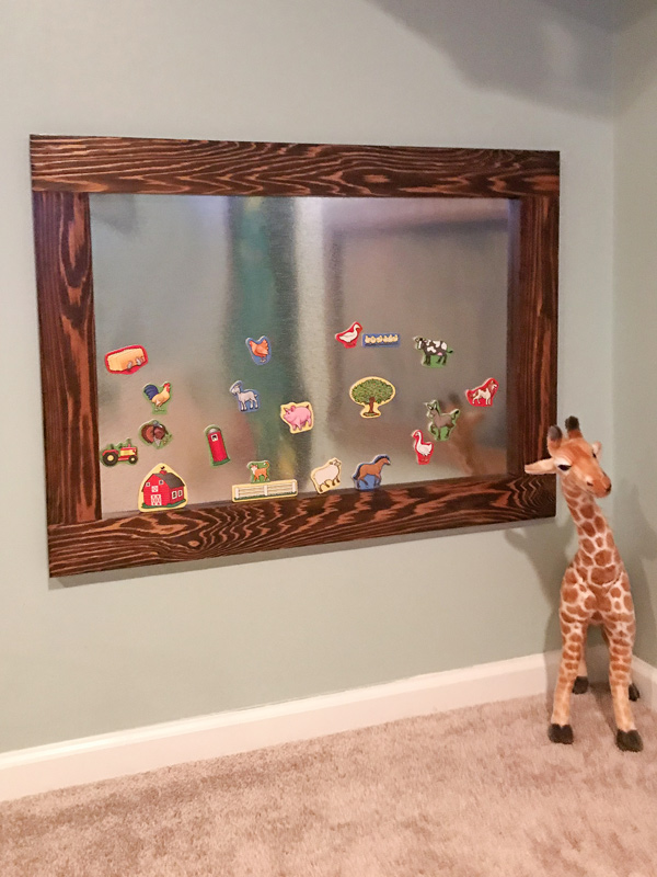 DIY magnetic board with kids magnets hung low on wall in kids playroom