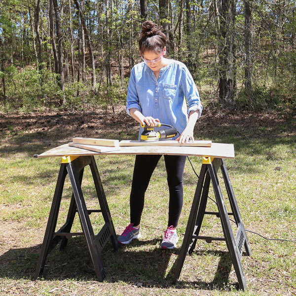 how to sand wood with woman sanding wood outside with orbital sander