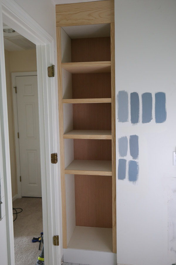 Trim out the frame of the DIY Built In Bathroom Shelves and Cabinet with wood
