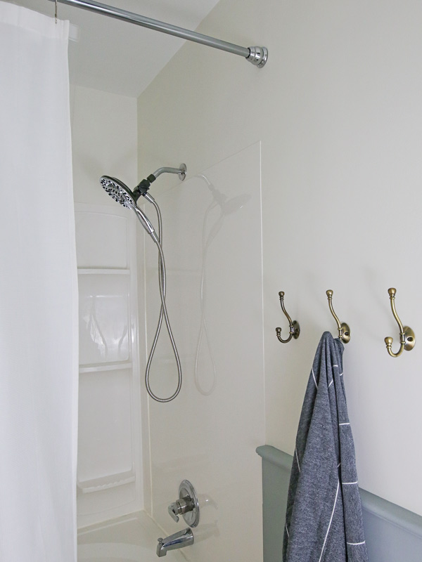 new shower surround and fixtures with brass towel hooks