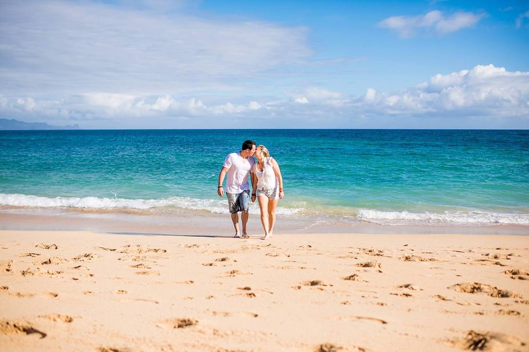 couple kissing on beach in maui, hawaii