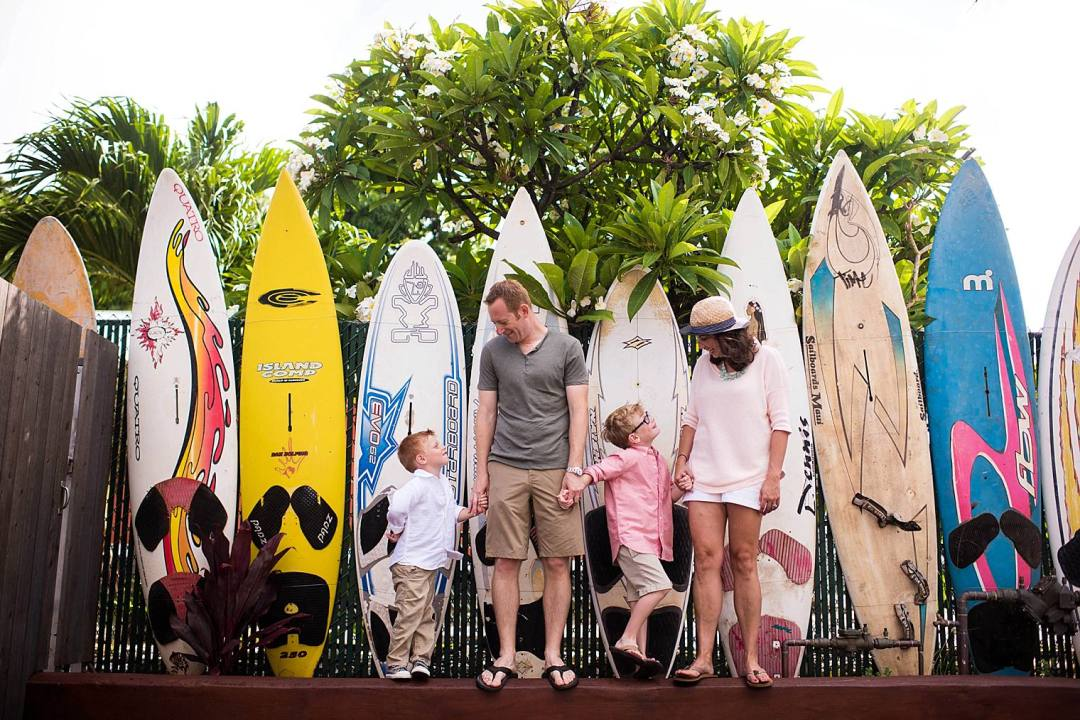 family with surfboard fence in Maui