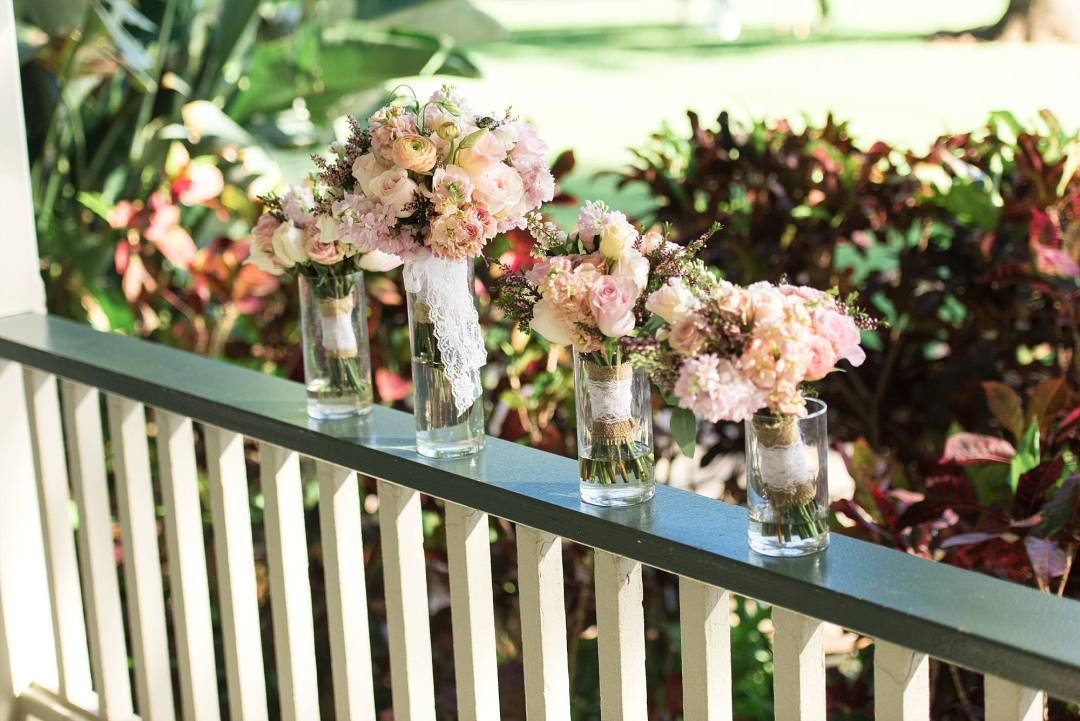 bride and bridal party's flowers arranged on a railing