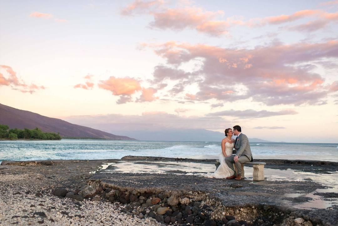 couple sitting kissing on bench near ocean