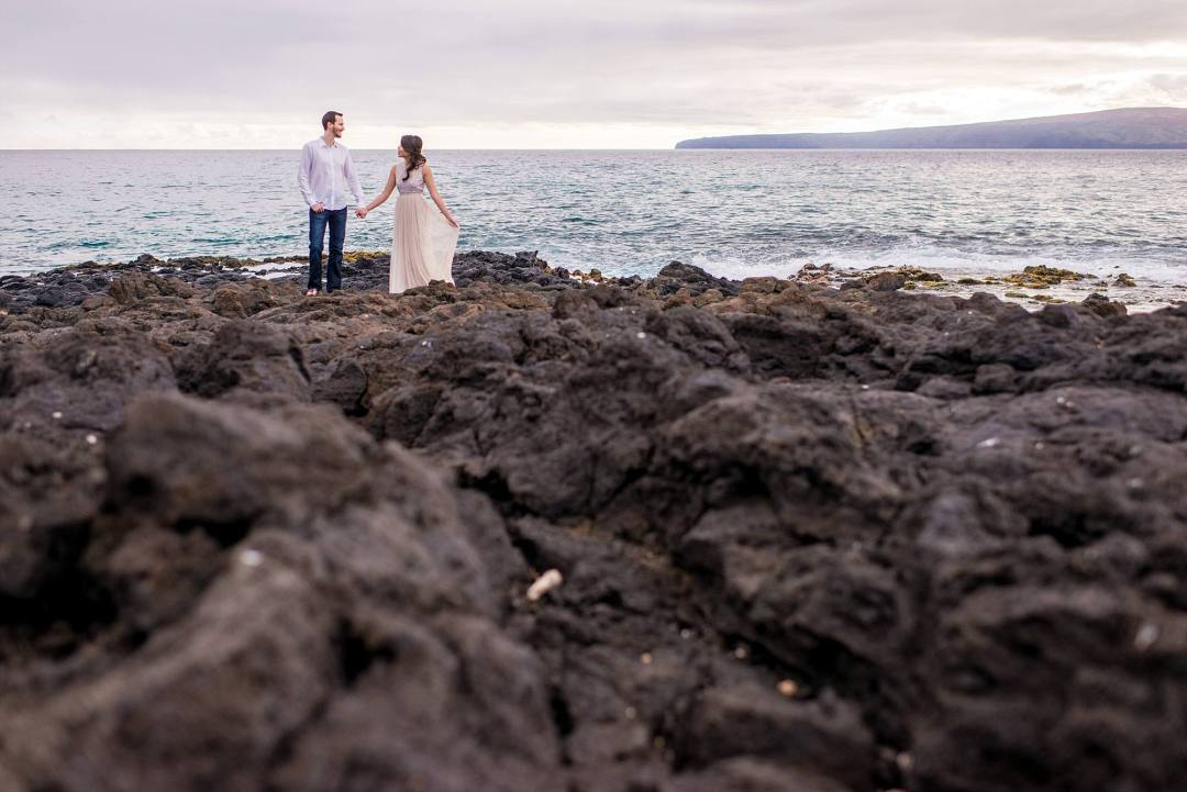 fiances standing on lava field woman holding dress out to the side