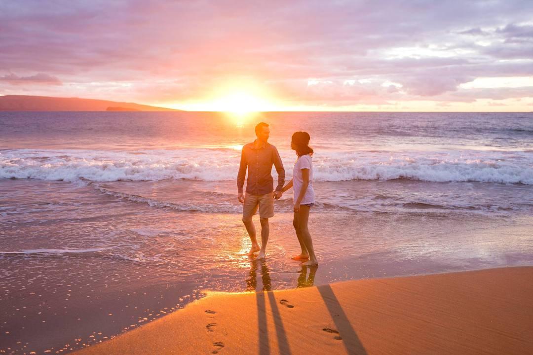 sunset beach photo couple walking through the waves