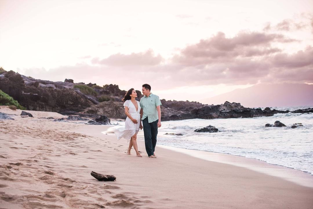 expecting couple walking down Maui beach hand in hand