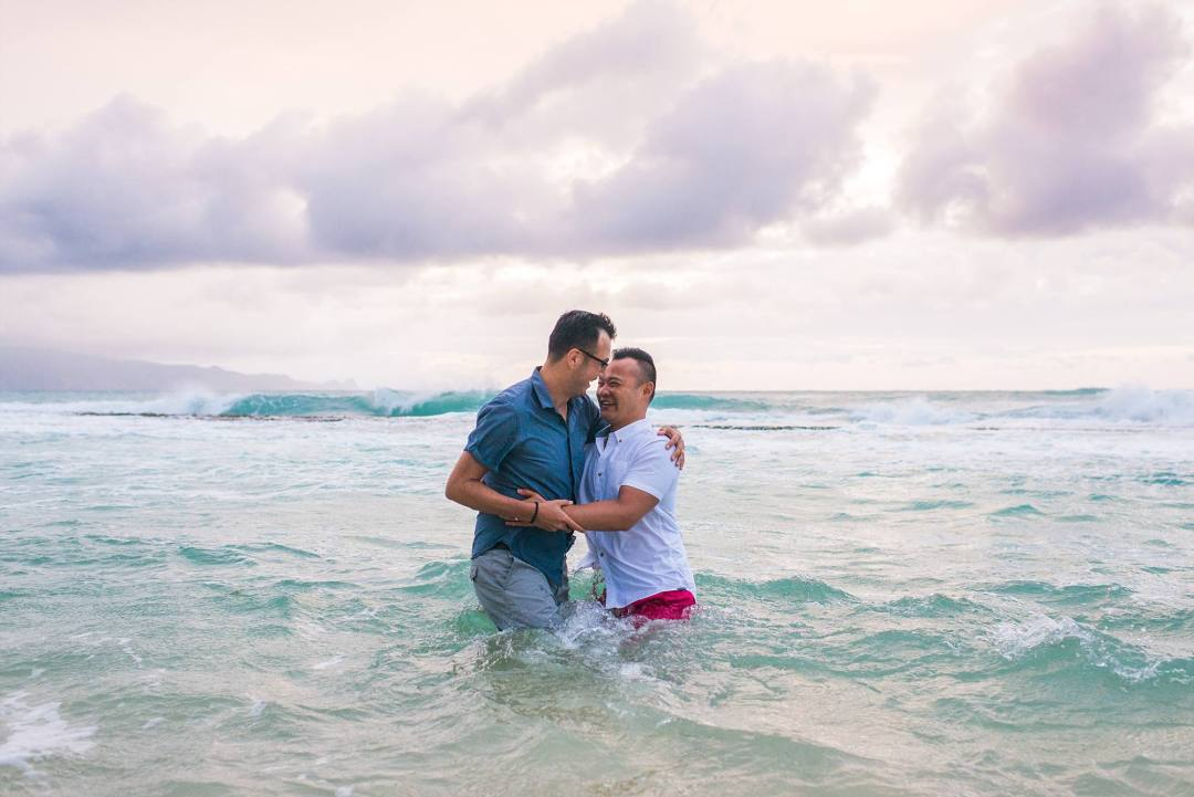 men laughing together and hugging while standing in the ocean, the waves making them unsteady