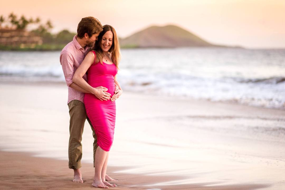 husband and wife pose for pregnancy shots on beach during their trip to Maui