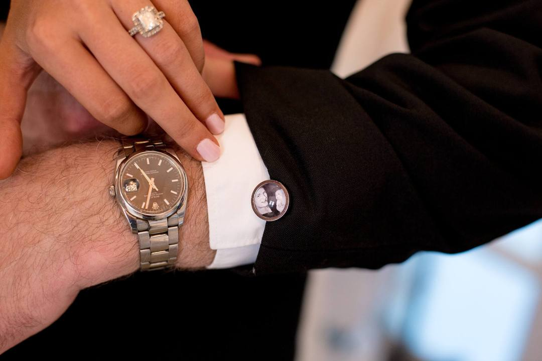 father of the bride showing off his watch and personalized cuff links