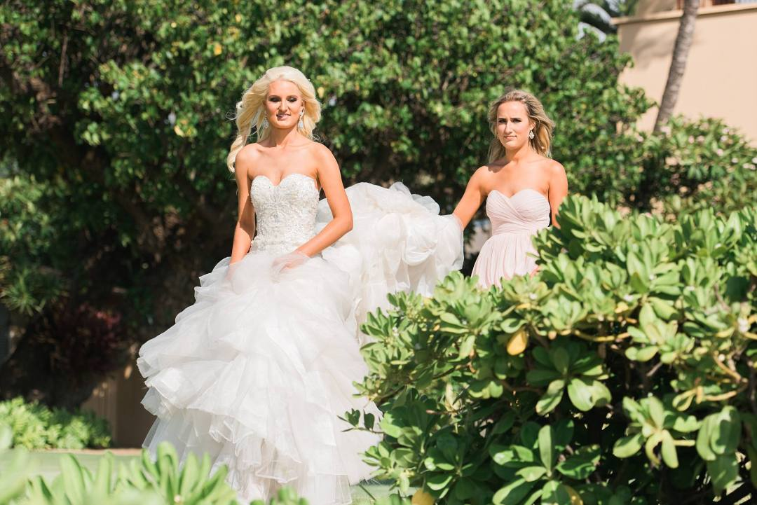 bride walking through tropical hawaiian trees with maid of honor holding up her dress
