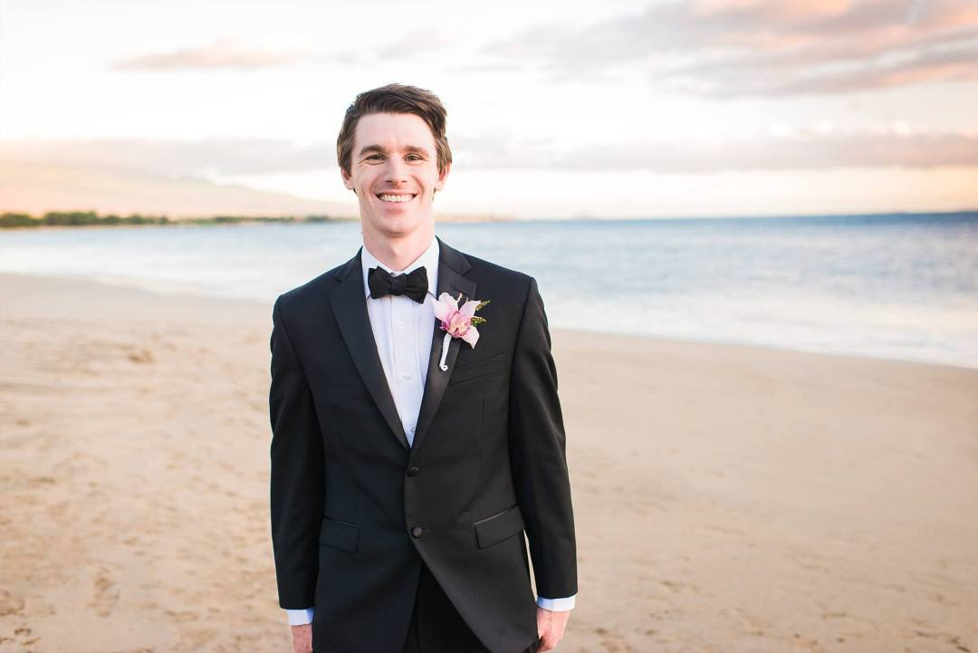 Groom looking handsome in tux and black bow tie with plumeria on lapel, on the white sand beach of Maui
