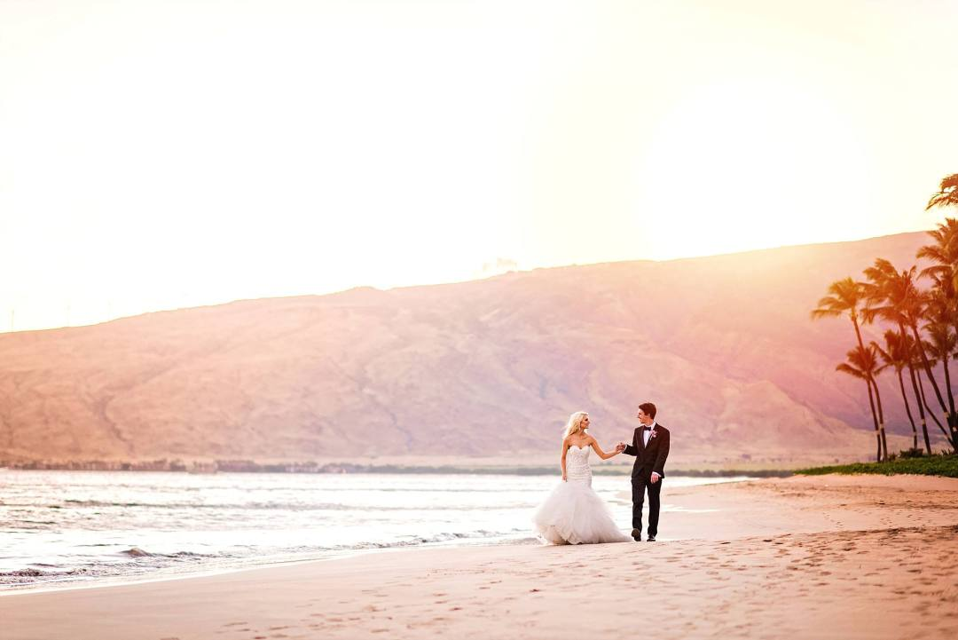 Pink sunset sky, West Maui Mountains in the distance and bride and groom walking on beach down towards the camera