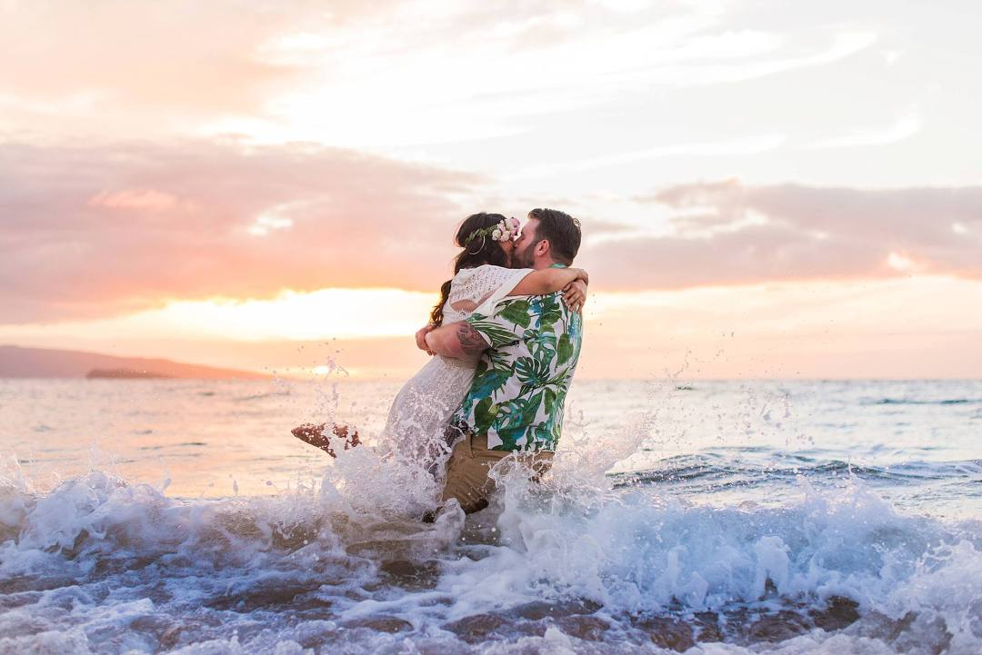 photo of a couple kissing in the ocean in maui