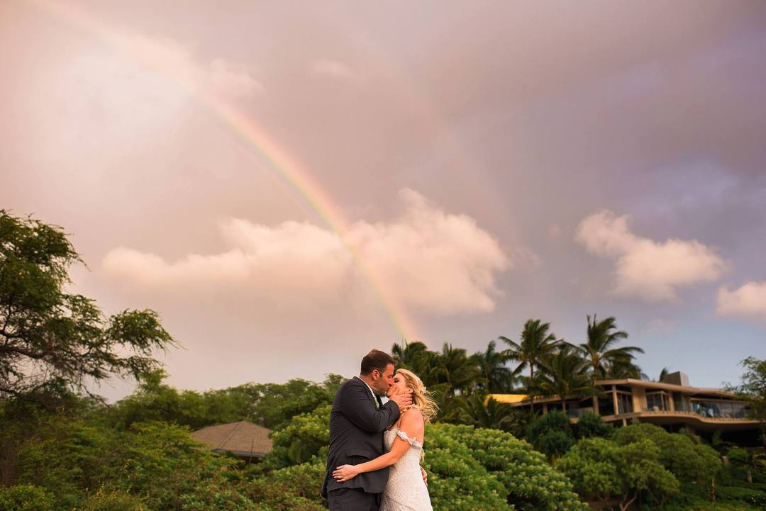 couple kissing under a rainbow in maui