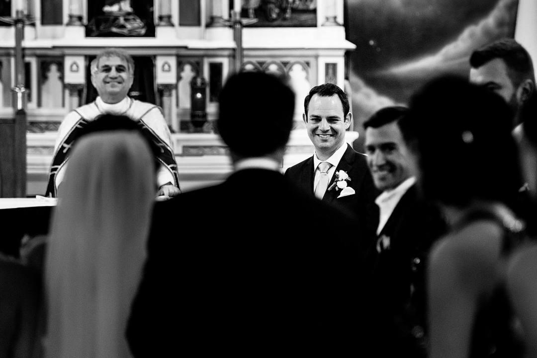 groom reacting to bride walking down the aisle
