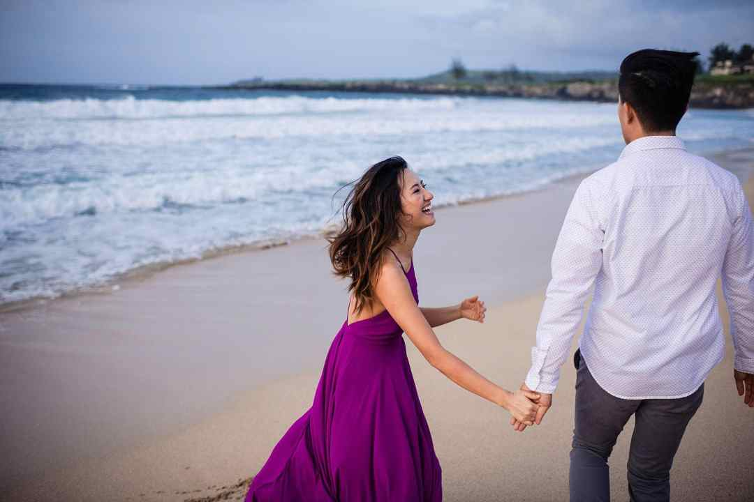 engaged couple playing on the beach in maui