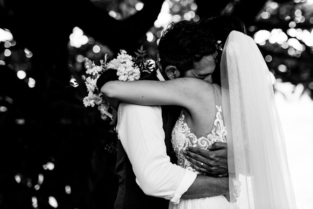 groom hugging bride in black and white