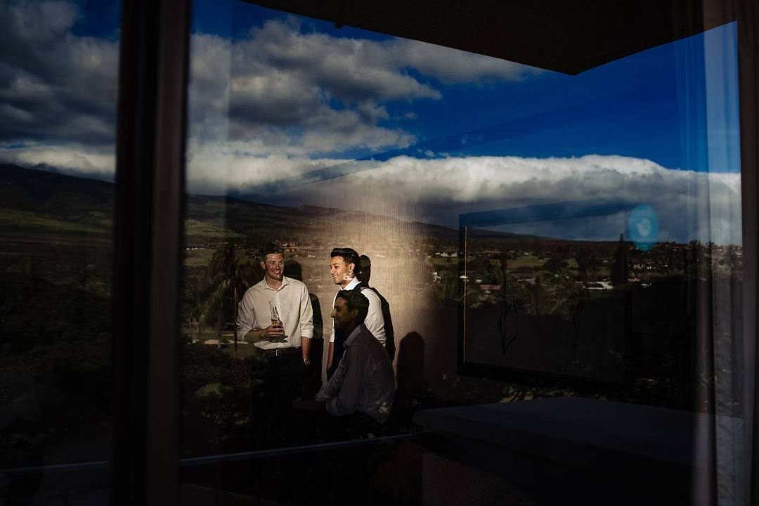 groom's reflection in window in hyatt maui