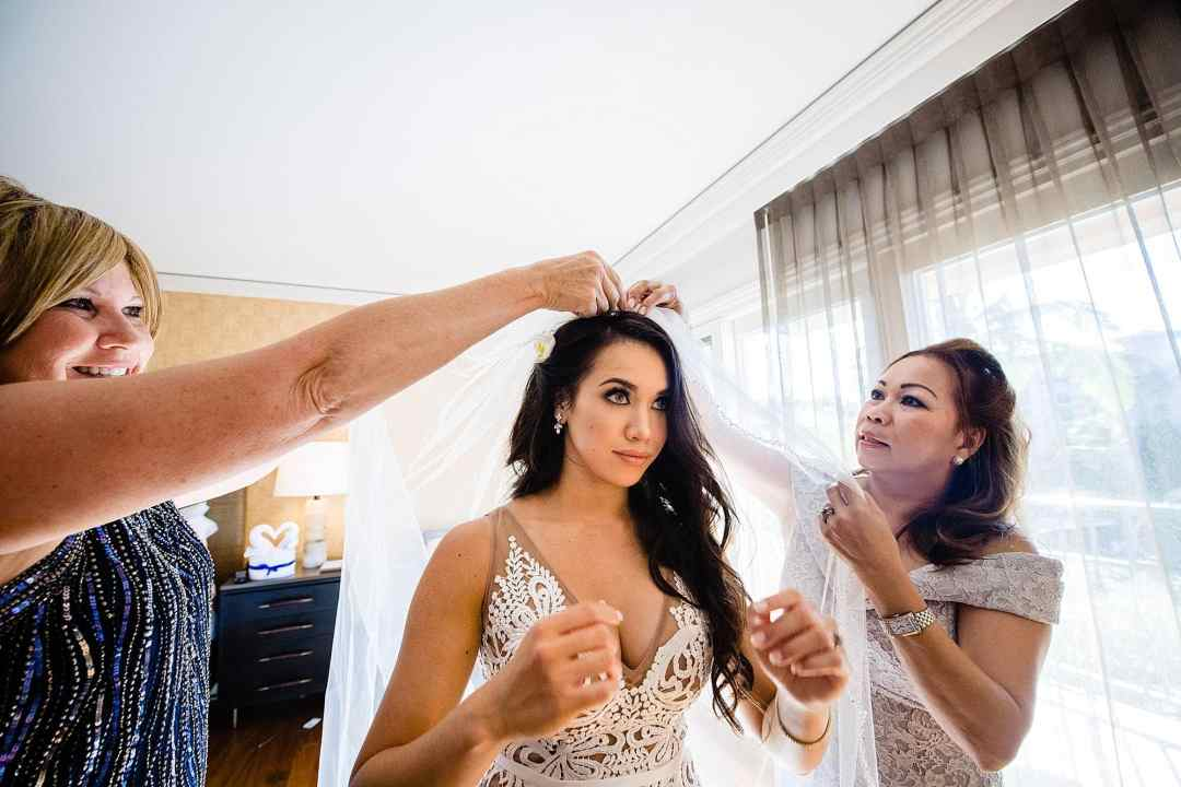 bride getting veil placed by mother