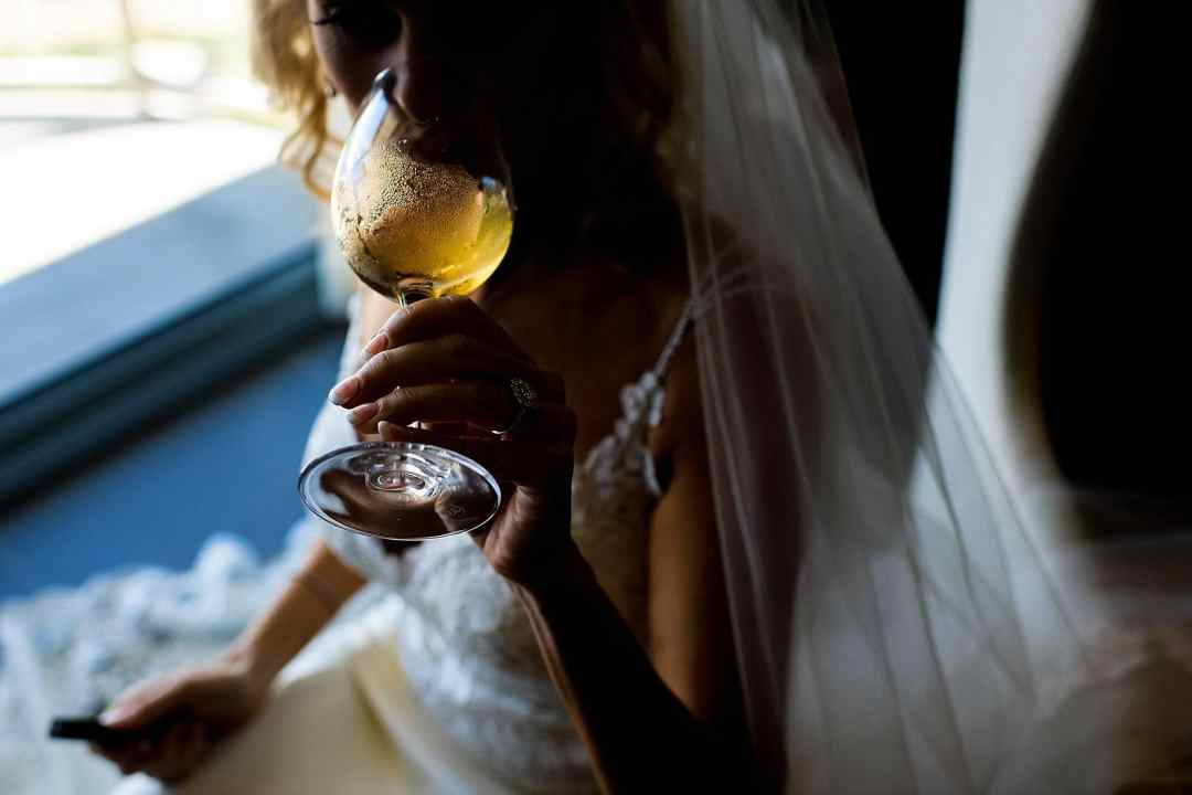 bride drinking wine before getting ready