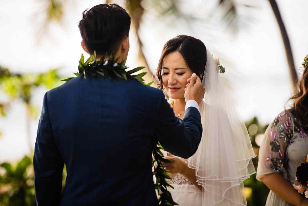 groom brushing bride's cheek during ceremony