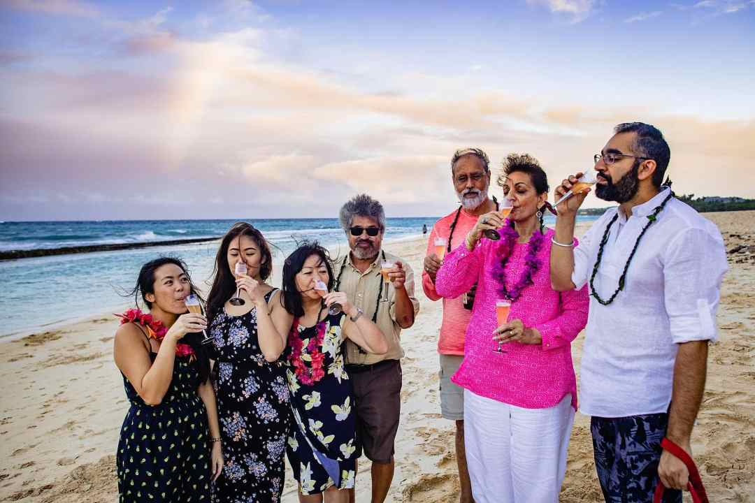 family drinking champagne on the beach after a proposal