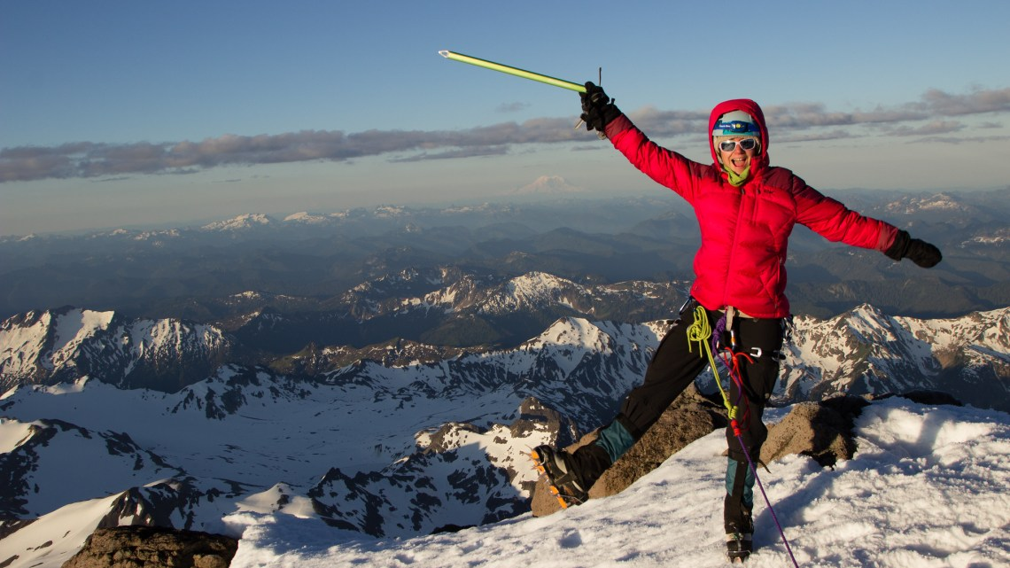 female mountaineering standing on top of Glacier Peak in Washington
