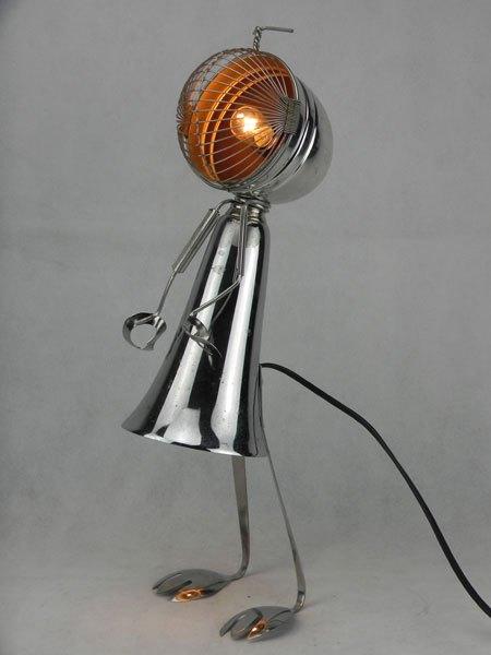 Couprille. Lampe féminine en métal. Assemblage de deux coupes de sport, une passoire, deux couverts et une pince à escargot.