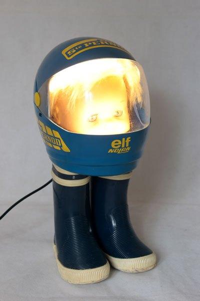 """Elf5. Baigneur casqué sur bottes. Assemblage: bac à glaçons en forme de casque """"ELF Nolan, écurie Sté Pernod"""", bottes d'enfant, tête de baigneur ."""