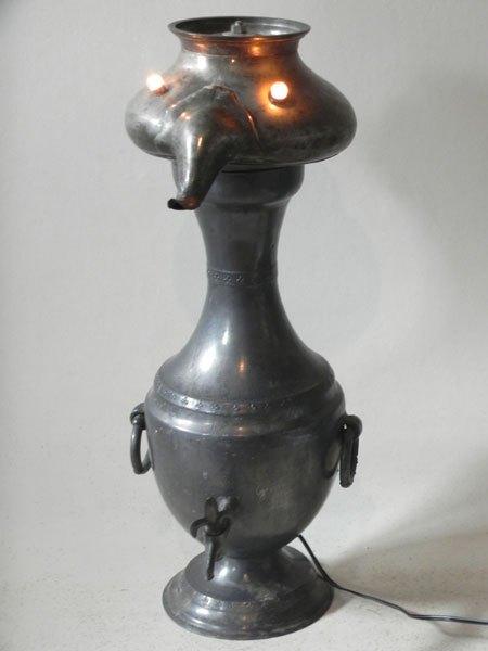 Etinteg. Personnage lumineux avec objets en étain. Assemblage d'une théière et d'un pot avec robinet.