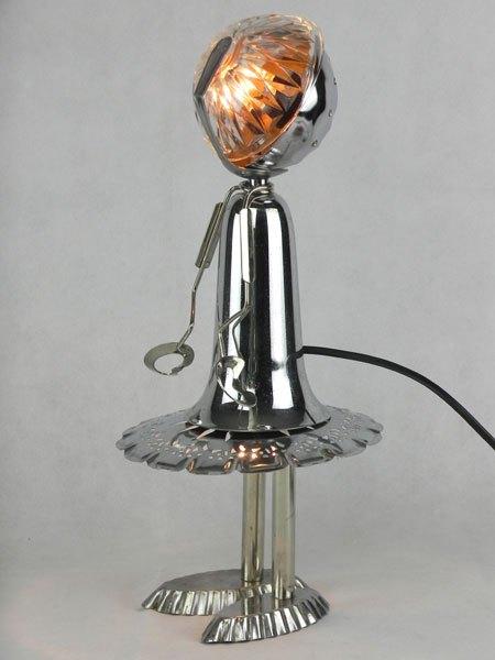 Fillaute. Fille en métal avec objets détournés. Assemblage lumineux: coupe de sport, ramequin, assiette ajourée, cuillère, pince à escargot et 2 moules à tartelettes.