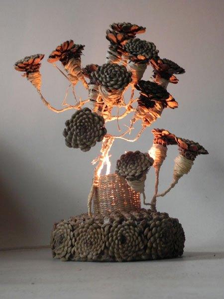 Fleurdepin. Couronne de fleur en pommes de pin recomposées. Avec ciment, osier, raphia, métal. Ecoconception, recyclage matière locale.