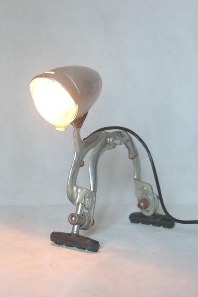 Freinalux. Optique de vélo ancien sur frein avec patins. Assemblage d'aluminium. Lampe sur pattes.