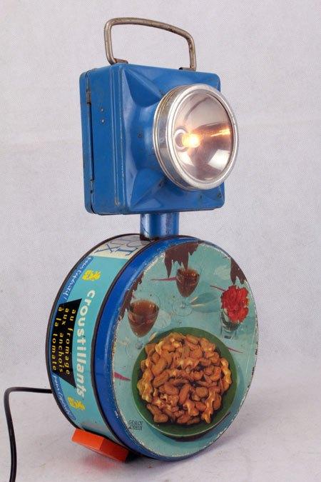 """Geslot. Lampe culbutos avec boite ancienne. Composition: boite de crakers """"GESLOT VOREUX"""" et lampe de poche ."""