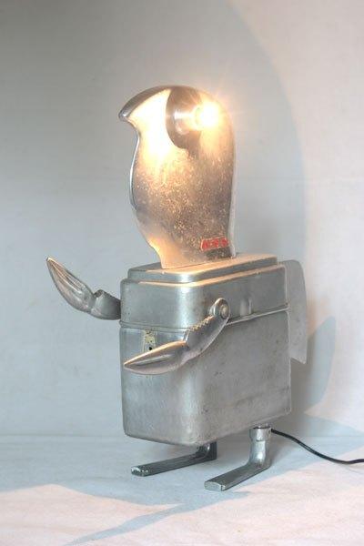 """Kymu. Sculpture homme oiseau aluminium assemblage d'éléments de trancheuse familiale en fonte d'aluminium, une boite gamelle """"MA.MOU.Marseille 1939"""", pince en forme de crabe et 2 clenches aux pieds."""