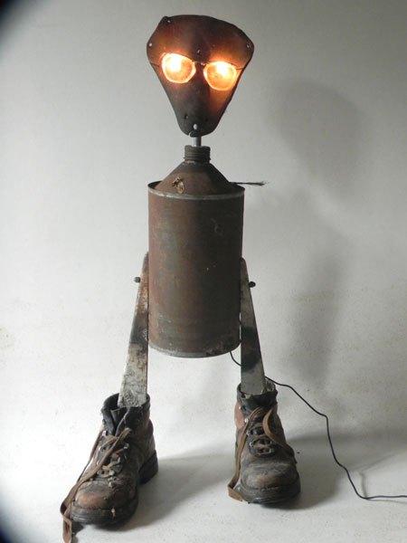 Loudillot. Sculpture lumineuse loup avec selle ancienne en cuir, bidon rouillé, godillots usés, équerres.
