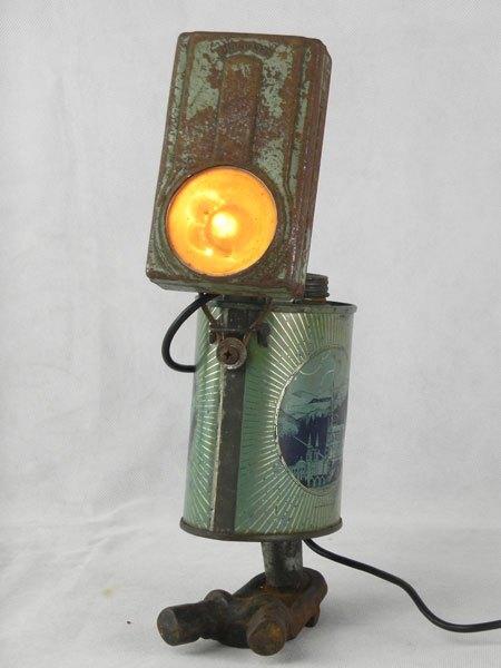 """Lourduz. Assemblage d'une lampe de poche et d'un bidon d'eau bénite """"Souvenir de Lourdes"""" avec une pièce mécanique."""