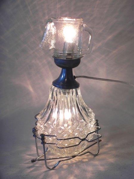 Lustroc. Détournement de verre assemblage de verrerie et broc. Personnage lumineux.