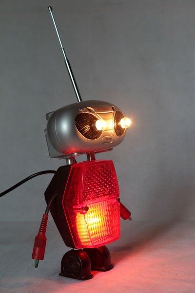Robadio. Robot radio et catadioptre, assemblage d'une mini radio (cadeau publicitaire), feu arrière de vélo, 2 prises électriques anciennes en bakélite et 2 fiches stéréo.