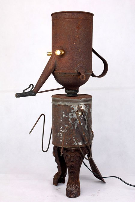 Rouilloir. Sculpture assemblage d'objets en métal rouillé, tôle et fonte. Composition: arrosoir, boite, pied en fonte, chausse pied.