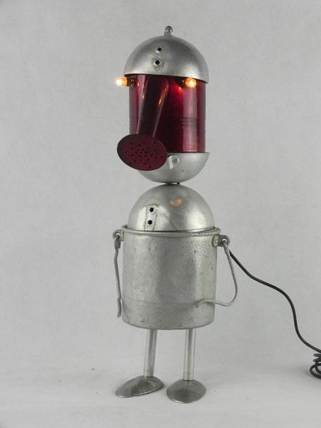 Gamsoir. Association lumineuse d'un arrosoir, un seau, trois louches et 2 cuillères, Détournement d'objets en aluminium.
